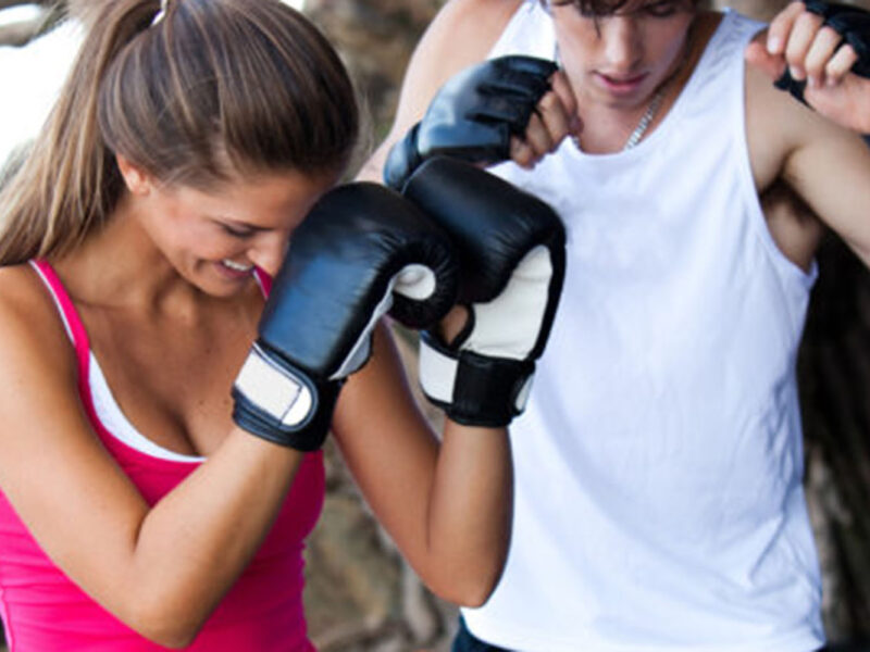 High angle view of a young couple outdoors, boxing for fitness. They are both looking down as if to see their stance. Vertical shot.